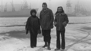 Hector sekä Pirjo ja Matti Bergström seisovat talvisessa satamassa.