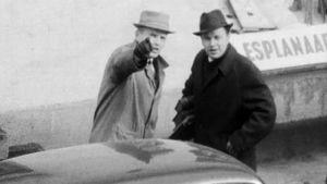 Utelias kamera -ohjelman tekijä Risto Vanari piilokameran uhrin kanssa Helsingin Esplanadilla henkilöauton vierellä. Vanari osoittaa miehelle kädellään kameran kätköpaikan.