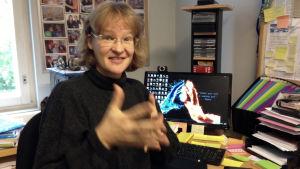en kvinna sitter framför en dator och gör en rörelse med händerna på teckenspråk