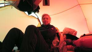 Kvinna med kort blont hår som sitter inne i ett tält. Det är fullt med kläder i tältet och i taket hänger också saker.