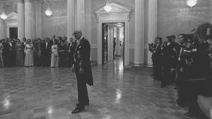 Tasavallan presidentin itsenäisyyspäivän vastaanotto Presidentinlinnassa 1975. Presidentti Urho Kekkonen seisoo yksin keskellä salia, taustalla vieraita ja valokuvaajia.