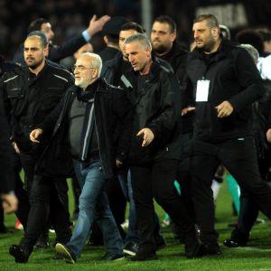 Klubbägare och livvakter stormar en fotbollsplan.