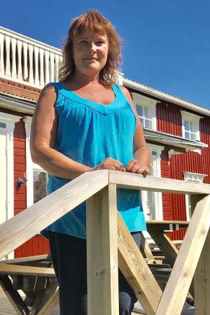 Marianne Långkvist som står på terassen med huset i bakgrunden.
