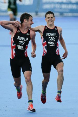 Alistair Brownlee hjälper brodern Jonathan över mållinjen i ett triathlonlopp i Mexiko.