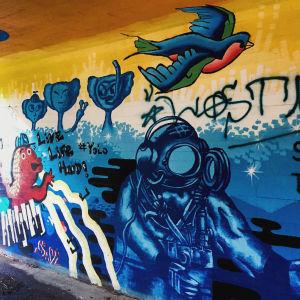 Värikäs seinämaalaus alikulkutunnelissa, jossa tekstit live life hard, yolo ja kuva astronautista ja linnusta.