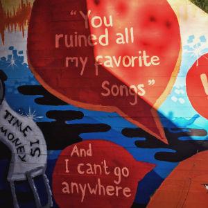 Värikäs seinämaalaus alikulkutunnelissa, jossa tekstit you ruined my favourite songs ja and now i can't go anywhere