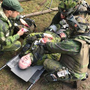 Sårad ligger på bår med tre rekryter som försöker hjälpa, under en militärövning.