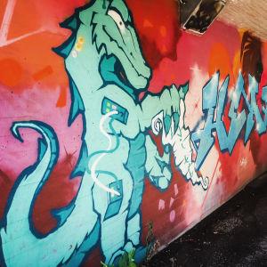 Graffititeos alikulkutunnelissa, jossa vihreäsävyinen lohikäärme.