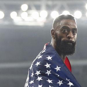 Tyson Gay framför strålkastarljusen insvept i den ameikanska flaggan.