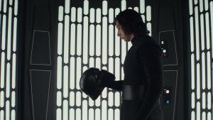 Kylo Ren (Adam Driver) håller i sin hjäm i handen och ser på den.