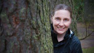 Kvinna tittar fram bakom en trädstam.