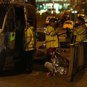 Kvinna sitter på trottoarkanten efter händelsen i Manchester och polisen finns på plats.