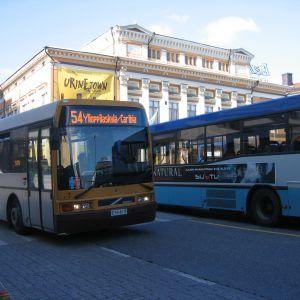 Två stadsbussar vid Salutorget i Åbo. I bakgrunden finns Åbo Svenska Teater.