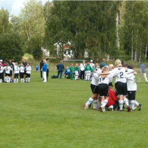 Fotbollsspelande flickor samlas i grupp före en match på gräsplan.