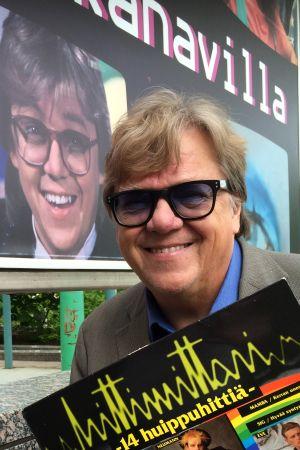 Mikko Alatalo poseeraa Ison pajan edessä Hittimittari levy kädessään.