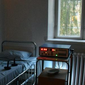 Personer står i mörkt rum intill sjukhussäng och elbehandlingsapparat.