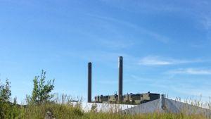 Två höga skorstenar höjer sig ovanför fyra industriella byggnader. Blå himmel. Grönt gräs och vita byggnader skymtar i förgrunden.