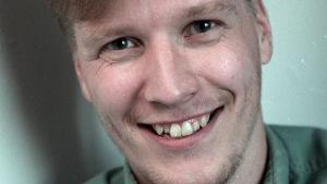 Kirjailija ja ohjaaja Reko Lundán katsoo nauraen kameraan.