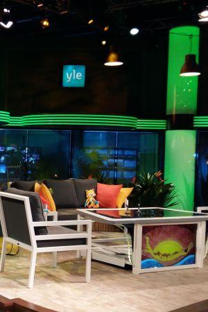 Människor diskuterar i kulisserna kring Yles studio för OS-sändningar.