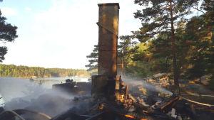 En skorsten står kvar efter bastu som brunnit till grunden.