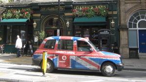 Brittilipun kuosissa oleva taksi pubin edessä Lontoossa.
