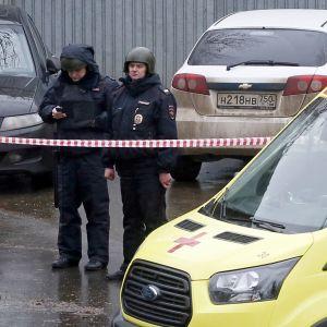 Poliser och ambulans står utanför en fabrik i Moskva där en person dödades.