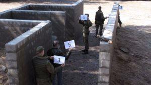 Några män i militärkläder står invid väggar uppmurade av betongblock, håller nummerskyltar i händerna.