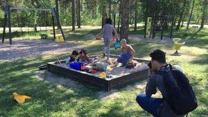 Barn leker i en sandlåda. En ung man med ryggsäck på ryggen fotograferar dem. Sommar, solen skiner. I bakgrunden syns gungor och klätterställningar.