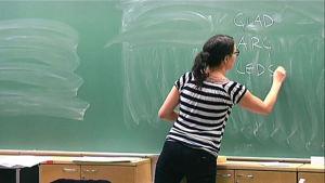 En kvinna skriver på en tavla i ett klassrum.