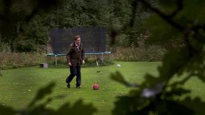 Olli pelaa jalkapalloa poikansa kanssa.