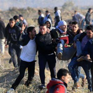 Palestinska demonstranter bar en sårad kamrat i sammandrabbningar med israeliska säkerhetsstyrkor nära gränsstängslet mot Israel öster om Gaza City på fredagen.