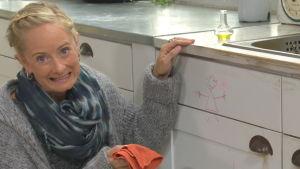 En bekymrad Alexandra de Paoli med trasa i handen. Ett barn har ritat en kritstrecksgumma på köksskåpet.