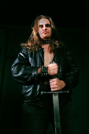 Lasse Grönroos poserar i läderrock, bart bröst och med ett svärd i handen.