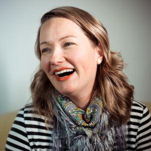 En kvinna med rågblont hår. Hon har på sig en randig tröja och en halsduk med fransar. Hon skrattar stort.