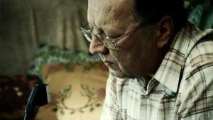 Mies (Sulevi Peltola) tuijottaa digiboksin scart-liitintä tietoiskussa.