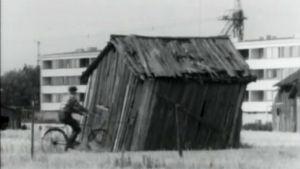 Mies pyöräilee vanhan kallistuneen ladon ohi, taustalla kerrostaloja.