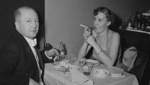 Tupakoiva pari ravintola Adlonin pöydässä.