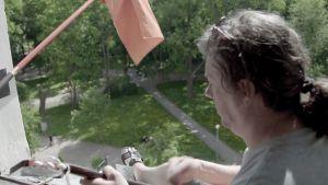 Andrei Holms soittaa balalaikkaa ikkunalaudalla dokumentissa Viipuri 360