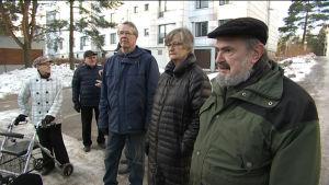 Fem äldre personer på en höghusgård.