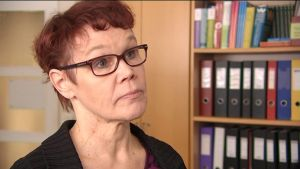 Kvinna med glasögon står vid en bokhylla med mappar.