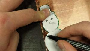 En hand ritar med grön tusch runt en pappersmall av en snögubbe, på en bit kopparplåt.
