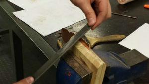 En snögubbe av kopparplåt är fastspänd i ett skruvstäd mellan två träklossar och filas med en metallfil.