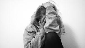 Svartvit bild på flicka som sitter och håller i huvudet för att symbolisera ångestkänslor.