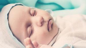 Pieni vauva nukkuu, pipo päässä.