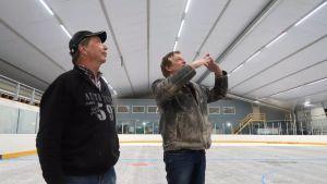 Två män tittar upp i taket i en idrottshall där säkerhetsbrister i konstruktionen upptäckts.