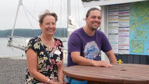 Sonja Petrell-Auvinen och Benjamin Lundin sitter vid ett bord ute. I bakgrunden syns en infotavla och en segelbåt.