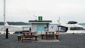 Två bord med bänkar står ute vid en pir. I bild synd två båtar och en rätt stor informationstavla för turister.
