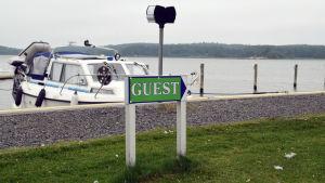 """En båt står förtöjd i en gästhamn. I förgrunden syns en grön skylt där det står """"guest""""."""