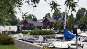 Båtar står förtöjda i en småbåtshamn. I bakgrunden skymtar en stor röd byggnad med en skylt där det står Strand.