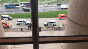 Knivhuggning utanför riksdagshuset, polisbilarna fotograferade genom ett fönster.